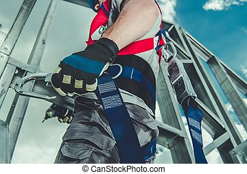 Safety Harness Equipment Closeup. Caucasian Contractor in His 30s on a Steel Building Frame. Working At Height Concept.