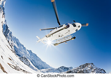 Heli Skiing Helicopter is landing on a ski slope in...