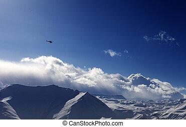 Helicopter above snowy plateau in evening. Ski resort Gudauri. Caucasus Mountains, Georgia.