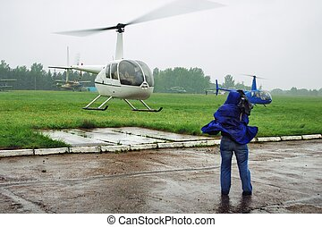 Helicopter launch under a rain - drops fly to cameraman