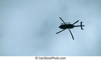 A modern, black helicopter hovers in the sky, as viewed from the bottom up. Silhouette of a modern helicopter hovering in the sky, the blades spin slowly.