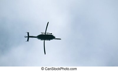 Helicopter bottom up view. Helicopter motionlessly hovered in the air. Silhouette of a modern helicopter in the sky, view from below. Slow motion, video footage. Copy space.