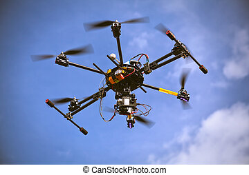 Flying helicopter drone is filming video in the blue sky