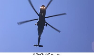Helicopter flies in blue sky in afternoon above ground