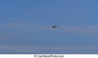 A helicopter flies in the blue sky low above the ground.
