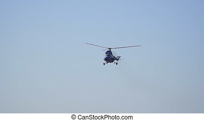 Helicopter flies in the clear sky