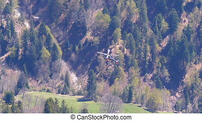 Helicopter flies in the Swiss Alps. Distant top view of a helicopter with rotating cavities against the backdrop of a mountain forest.