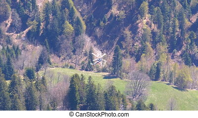 Helicopter flies in the Swiss Alps. Distant top view of a...