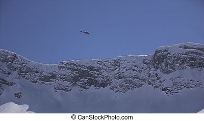 Helicopter fly above snowy peaks of mountains. Blue sky. Sunny day.