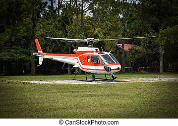 helicopter flying down on field on the forest / white red fly helicopter rescue