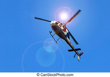 Helicopter flying under bright sun light and blue sky