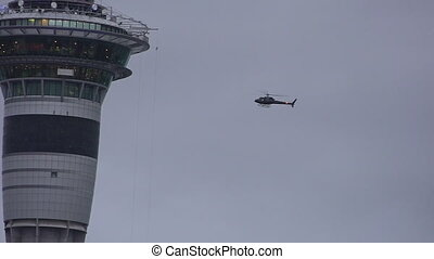 Helicopter hover near the top of Sky Tower in Auckland New Zealand. It's 328m (1,076 ft) making it the tallest free-standing structure in the Southern Hemisphere.