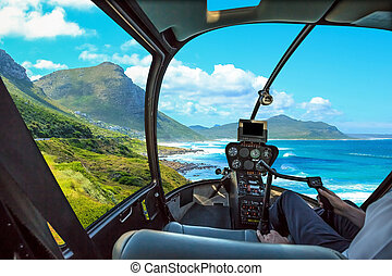 Helicopter cockpit flies in Misty Cliffs, Cape Peninsula in South Africa, with pilot arm and control board inside the cabin.