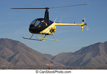 Helicopter in flight with mountains in the background.