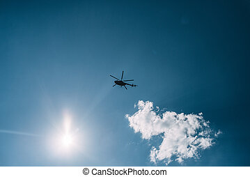 Helicopter in the sky and bright sun