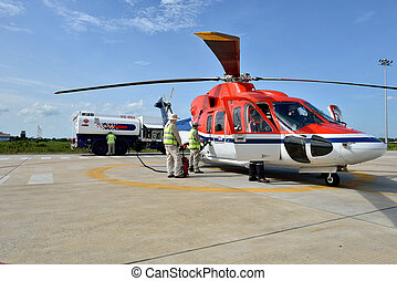 Helicopter is refuel - They is refuelling helicopter at the...
