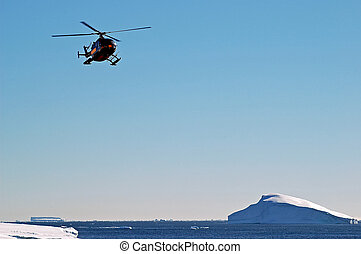 Helicopter over Antarctic iceberg scenery - A helicopter in...