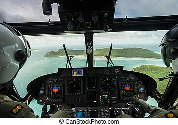 Helicopter pilot seen from behind above the island, Thailand