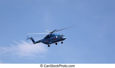 Helicopter quickly flies in blue sky in afternoon above ground