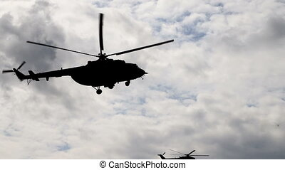 Helicopter (silhouette) flies in the sky close up.