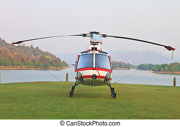 helicopter standing on landing strip in airfield near lake...