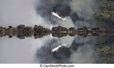 Helicopter throwing water to fire with huge smoke reflection...