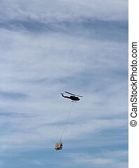 Helicopter Towing Freight in Alaska - A helicopter tows...