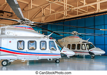 Two white helicopters in hangar