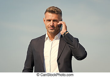 Hello, answer the phone. Businessman call on mobile phone. Handsome man with cell phone outdoors. Business communication. Phone for professional use. 3G. 4G. Mobile lifestyle. New technology