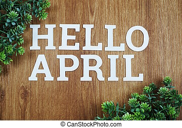 Hello April Alphabet Letters with green plant on wooden background
