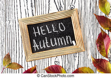 Hello autumn greeting text on chalkboard. Top view.