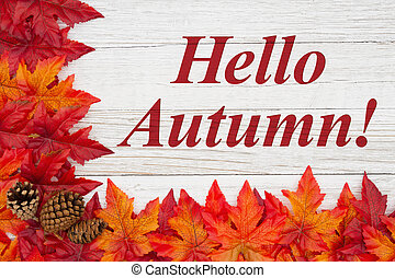Hello Autumn message with red and orange fall leaves with pine cones on weathered wood