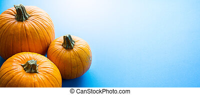 Hello autumn; thanksgiving holiday party background with autumn pumpkin on blue background