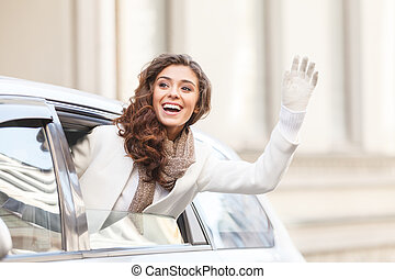 Hello! Beautiful young woman looking out from a car saying hello and waving to someone