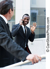 Hello! Cheerful young African man in formalwear moving up by stairs and waving to his colleague