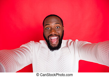 Hello dear followers. Photo of funny dark skin man holding telephone making carefree selfies wear white knitted sweater isolated red background
