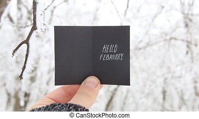 Hello February creative concept, man holding a card with...