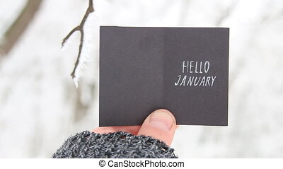 Hello January creative concept, man holding a card with text