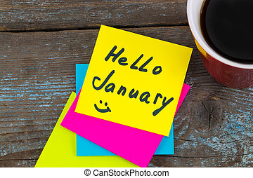 Hello January - handwriting in black ink on a sticky note with a cup of coffee, New Year resolutions concept