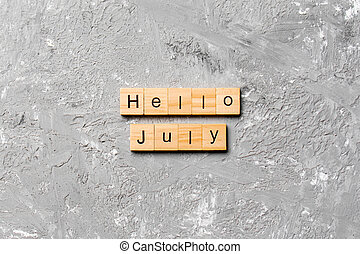 hello july word written on wood block. hello july text on table, concept