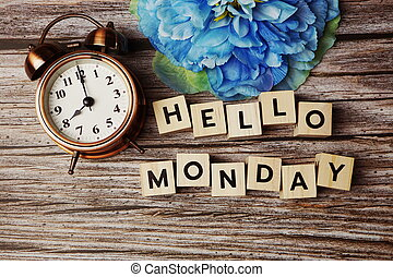 Hello Monday alphabet letter with alarm clock on wooden background