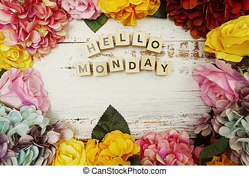 Hello Monday alphabet letter with colorful flowers border frame on wooden background