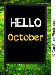 HELLO OCTOBER message on sidewalk blackboard sign against...