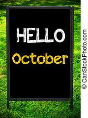 HELLO OCTOBER message on sidewalk blackboard sign against...
