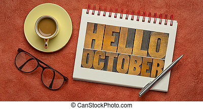 Hello October - letterpress wood type blocks typography in a spiral notebook with a cup of coffee