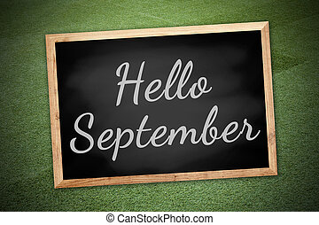 Hello Septemberconcept on chalk board and green field background and texture