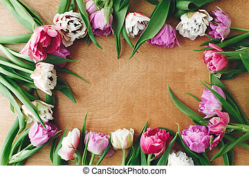 Hello Spring. Floral Greeting card. Beautiful double peony tulips frame flat lay on wooden table, space for text. Colorful pink and purple tulips. Happy mother's day. International women's day.