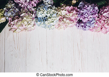 Hello spring. Happy mothers day. Women day. Beautiful hydrangea flowers on rustic white wood, flat lay. Colorful pink,blue,green,white border of hydrangea, greeting card with space for text.