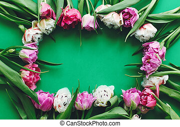 Hello Spring. Stylish Floral Greeting card. Beautiful double peony tulips frame flat lay on green paper, space for text. Happy mother's day. International women's day.