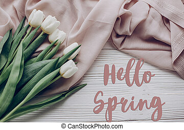hello spring text fresh sign. stylish white tulips on beige soft fabric and rustic wooden table background top view. flat lay. soft light, tenderness moment.